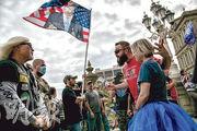 美國密歇根首府蘭辛的州議會前,支持特朗普的民眾(右)與反特朗普的人周日起爭執。(法新社)