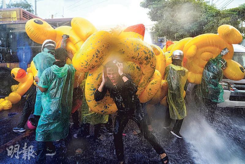 泰國示威者昨以吹氣膠鴨抵擋警方的水炮。(路透社)