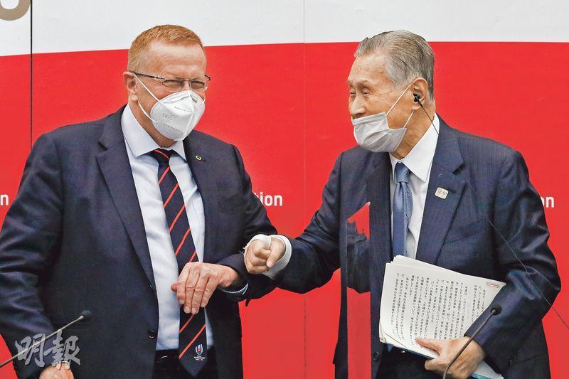 日本疫情嚴重,東京奧運協調委員會主席科茨(左)與東京奧運籌委會主席森喜朗(右)周三出席聯合記者會時,互碰手肘打招呼,但森喜朗戴口罩時鼻孔外露,不符標準。(法新社)