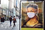 韓國首爾街頭昨日出現一幅戴上口罩及頭套的蒙娜麗莎肖像,呼籲民眾戴口罩防疫。(路透社)
