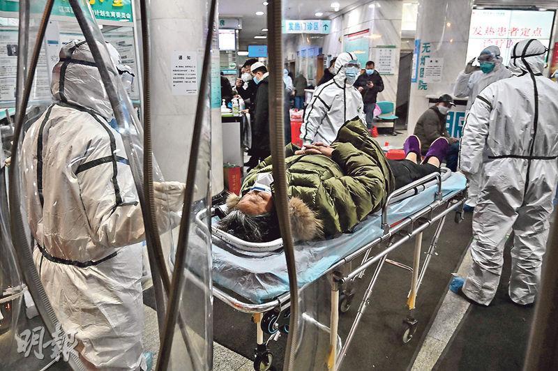 CNN昨報道,內地官方保密文件稱武漢疫情初期,當局處理失當及隱瞞有關數據。圖為1月25日,醫務人員將新冠患者送達武漢市紅十字會醫院。(法新社)