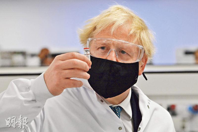 英國首相約翰遜周一(11月30日)到訪位於威爾斯北部城市域斯咸的藥廠,拿起一支由阿斯利康和牛津大學研發的新冠疫苗小瓶。(法新社)