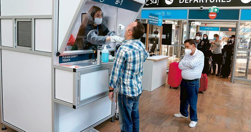 現時旅客登機前一般要取得新冠病毒陰性證明,或直接在機場做快速檢測,例如以色列古里安國際機場就特設新冠病毒快速檢測中心。圖為工作人員周三為乘客採樣。(法新社)