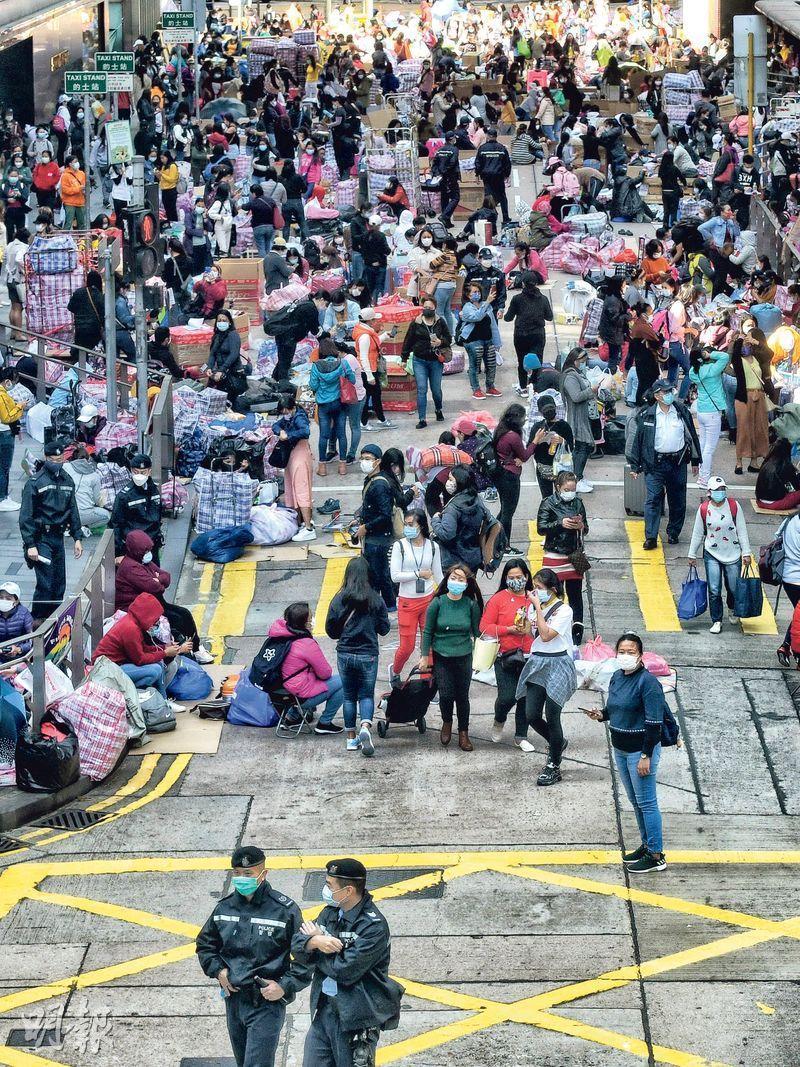 第四波疫情仍然嚴峻,但市面人流未減,大批外傭昨在中環如常聚集,警方上午曾到場派傳單,提醒在場者不可違犯二人限聚令。(朱安妮攝)