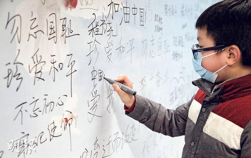 在南京大屠殺死難者國家公祭日前夕,江蘇南京多地舉行活動,悼念遇難同胞。圖為12月12日,在南京地鐵雲錦路站,一名小學生在「南京大屠殺死難者國家公祭日和平許願牆」上書寫和平心願。(新華社)