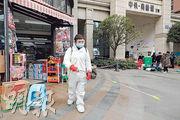 四川成都日前疫情反彈,出現數宗本土確診病例。圖為12月11日,一名醫務人員在引發疫情反彈的郫都區一處社區周圍消毒。(新華社)