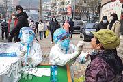 遼寧大連爆發新一波疫情,自前日起一連3天安排全民核酸檢測。圖為昨日市民在街頭檢測。(中新社)