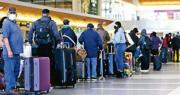 周二有民眾在洛杉磯國際機場排隊辦理登機。專家憂慮民眾在假期增加出行探望親友,可能令聖誕感染群組湧現。(法新社)