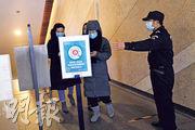 北京連續兩天出現無症狀感染者(隱形患者),官方稱疫情呈「多點散發態勢」。昨在北京街頭,有保安指示人們進入商店前掃描二維碼,以追蹤其健康狀况。(路透社)