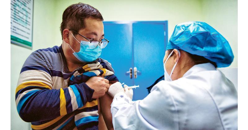 內地多地陸續展開新冠疫苗重點人群接種工作。圖為25日陜西一名機場人員接種新冠疫苗,為陝西首針。首批參加接種的「重點人群」是海關、口岸邊檢、口岸進口冷鏈物品運輸及醫療衛生機構的一線工作人員等。(新華社)