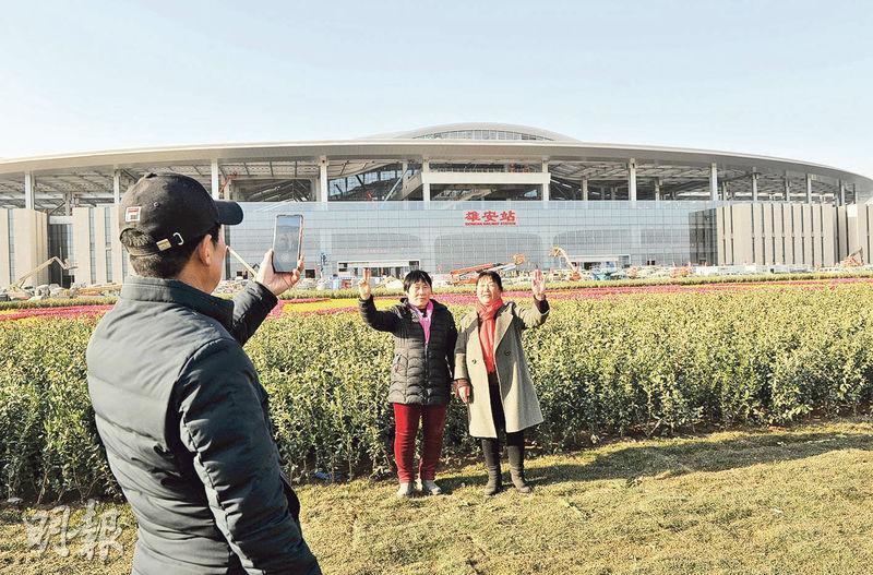 雄安居民24日在雄安站前拍照。(中新社)