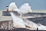 風暴「貝拉」吹襲英國,昨日當地一處有防波堤和燈塔的海邊有巨浪拍岸。(法新社)