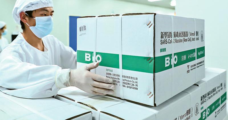 國務院聯防聯控機制昨(12月31日)宣布,國藥集團中國生物的新冠病毒滅活疫苗已獲國家藥監局批准附條件上市。國家衛健委承諾將為全民免費提供新冠疫苗,並展開全民接種。圖為去年12月25日,工作人員在國藥中生北京研究所疫苗分包裝車間工作。(新華社)