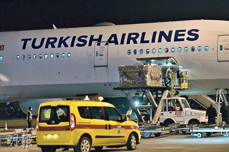 中國向土耳其運送首批300萬支新冠疫苗,周三運抵土耳其首都安卡拉,搬運工人正在卸貨。(新華社)