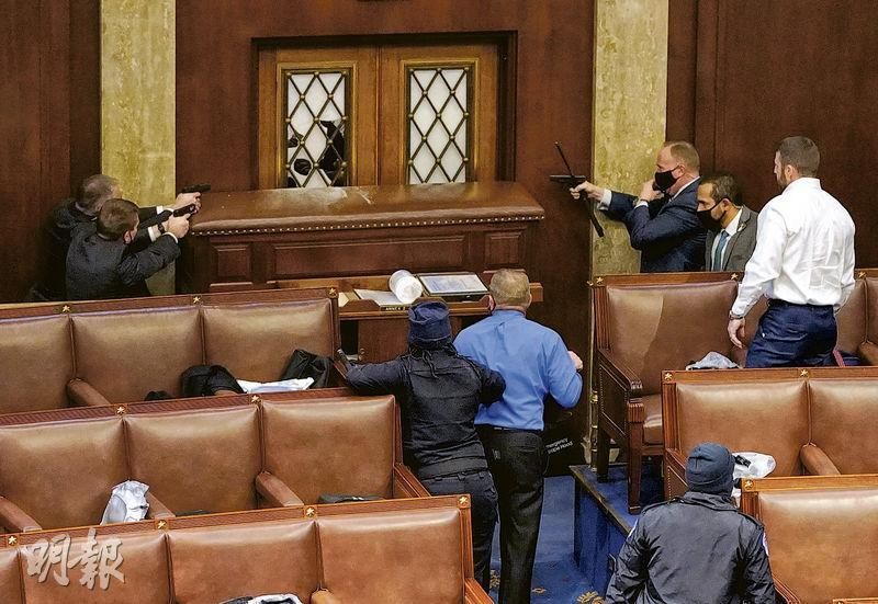 美國國會警察周三擎槍指向眾議院大廳一道被破壞的門,並以枱等堵着,防止示威者闖入。(法新社)