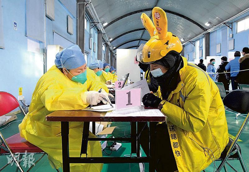在北京海殿區的疫苗接種點,有外賣員前日在醫護人員的指示下,填寫有關資料。(新華社)