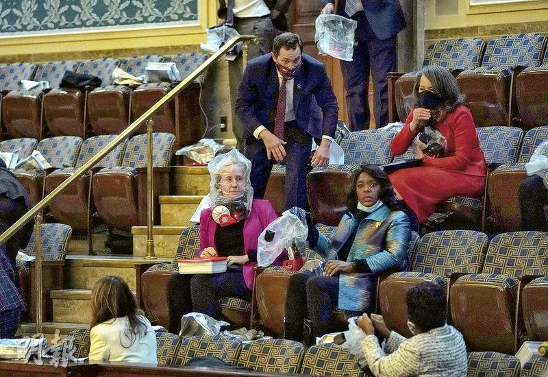 美國眾議院大廳周三舉行聯席會議確認選舉人團投票結果期間,有示威者企圖闖入,警方發射催淚氣體驅散,議會內的人拿出椅下的防毒頭罩套在頭上。(法新社)