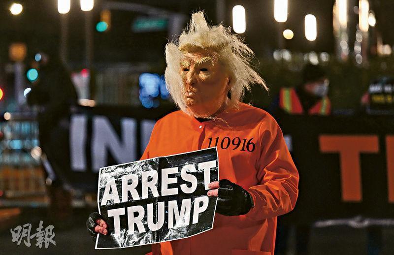 美國紐約市周三有男子打扮成總統特朗普穿上囚衣的樣子,到當地的特朗普國際酒店大廈抗議,手上的標語寫道「拘捕特朗普」。(法新社)