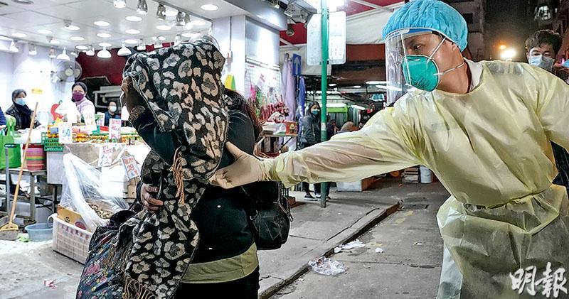 新填地街20至26號累計25居民染疫,4幢相連的唐樓居民須接受強制檢測,與確診者同層更須強制檢疫。昨晚近7時,新填地街26號再多一名居民被醫護人員接走。(楊柏賢攝)