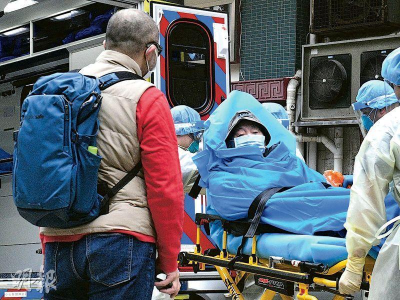 徐先生(左)的父親(擔架上)於周日被送往亞博檢疫,但近日天氣寒冷,徐先生接獲父親來電,說在牀上「凍到唔敢坐起身」。(林靄怡攝)