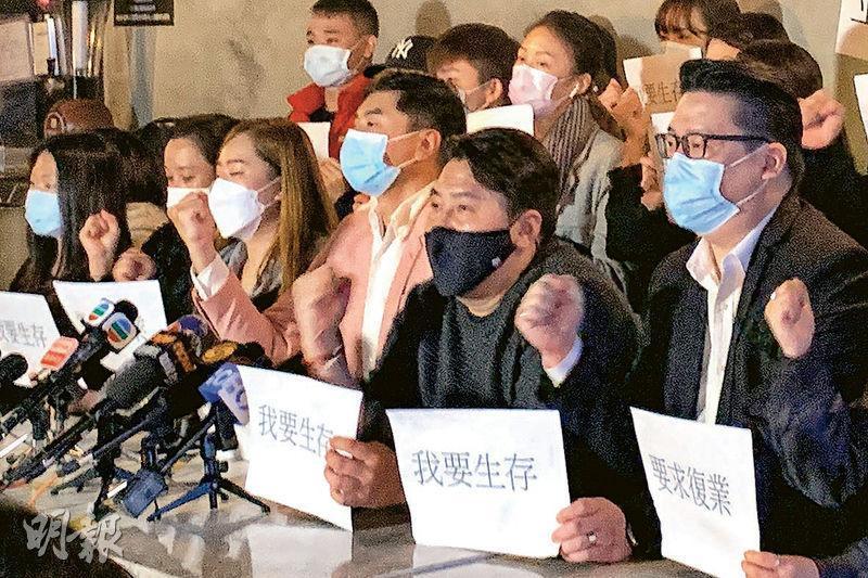香港酒吧業協會副主席錢雋永(粉紅西裝者)昨聯同多間酒吧負責人召開記者會,要求政府盡快批准酒吧有限制下復業。(丘萃瑩攝)