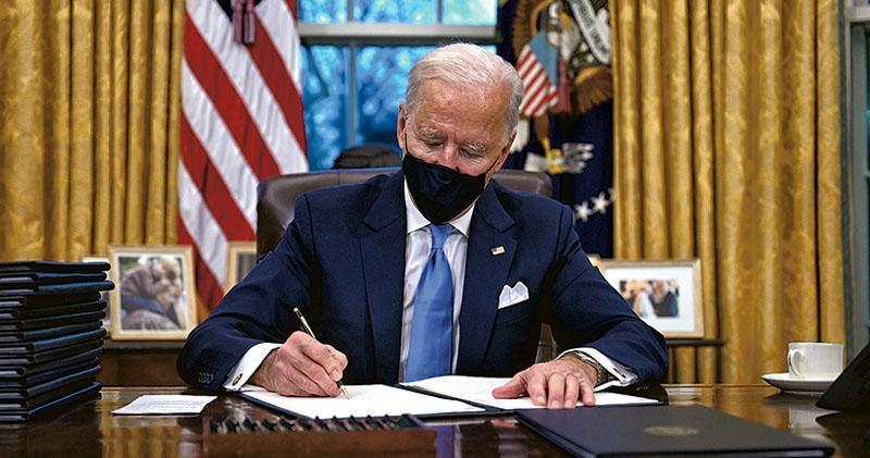 美國總統拜登周三(20日)宣誓就職後,於白宮橢圓形辦公室簽署多個行政命令,包括重新加入《巴黎協定》、停止退出世衛組織程序、取消對多個穆斯林國家的入境禁令,以及應對新冠疫情的措施。(法新社)
