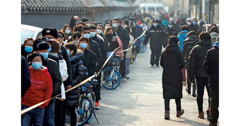 北京大興區本土確診者曾在市中心活動,位於北京中心的西城區及東城區昨起一連兩日為全區民眾作核酸檢測,不少檢測站外大打蛇餅。圖為昨日北京市民正排隊等待檢測。(路透社)