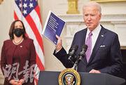 美國總統拜登(右)周四手執文件,在白宮談及政府的抗疫計劃,副總統賀錦麗(左)在旁聆聽。(路透社)