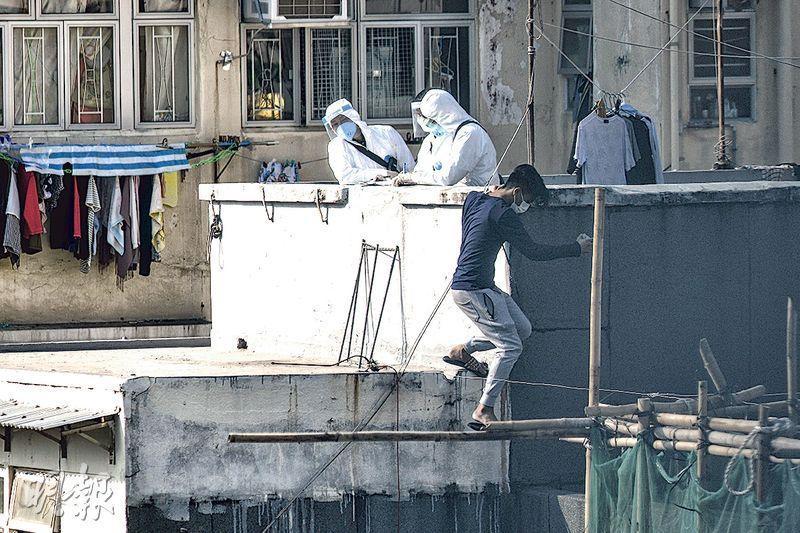 在受限區域內,居民須留在其處所並按政府安排接受強制檢測。昨晨一名青年站在大廈天台,手持身分證,有政府人員上前了解,該青年便跳到毗鄰大廈的天台離去。(馮凱鍵攝)