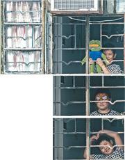 被困在家的小男孩不愁寂寞,透過家中窗戶看到記者鏡頭,一時扮鬼臉一時擺出心形動作,又戴上蜘蛛俠面具,拿出各種珍藏玩具在窗前展示。(馮凱鍵攝)