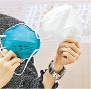 去年4月醫管局向傳媒介紹當時新引入的NASK納米纖維呼吸器(右),作為N95呼吸器(左)的替代品,當時口罩表面未印有規格。(資料圖片)