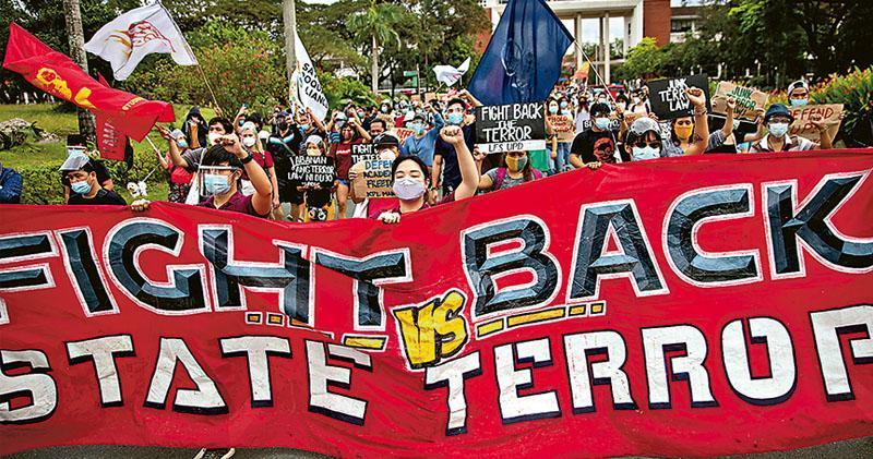 菲律賓大學的學生及聲援者上周二(19日)在奎松市校內示威,抗議軍方單方面取消禁制警察、士兵進入該所國立大學的協定。(路透社)