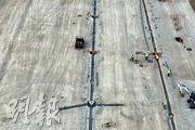機場三跑地盤爆發新冠病毒疫情,9名染疫工友中有7人涉飛行區地面燈號系統興建的工程。圖為早前工程人員安裝跑道燈。(資料圖片)