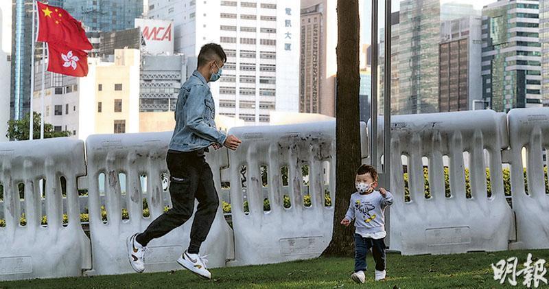 教育局提出,替代高中通識科的新科目要讓學生達到的學習成果,首項便是「了解香港特別行政區的憲制基礎、與國家的關係,和國家的最新發展,從而探究兩地互動發展的機遇和挑戰」。圖為家長帶同孩子在添馬公園國旗下附近草地遊玩。(李紹昌攝)