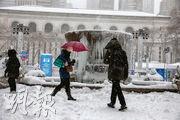 紐約市周一經歷暴風雪,布萊恩特公園的噴水池結出冰柱,有民眾冒雪出行。(新華社)