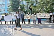 緬甸中部城市曼德勒的醫學大學前昨日有示威者拿着「人民反對軍事政變」的標語,抗議周一發生的軍事政變。(法新社)
