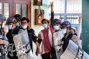 緬甸城市曼德勒有學生因抗議軍事政變被捕,周五押送法院,部分人做出象徵反抗威權獨裁、支持民主的三指禮。(路透社)