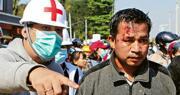 緬甸首都內比都昨有反對軍事政變的示威者頭部受傷流血,醫護人員在場協助他。(路透社)