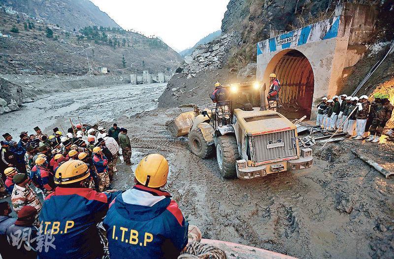 印度救援人員周一(8日)用大型機械清理一條在周日遭山洪衝擊的隧道。(路透社)
