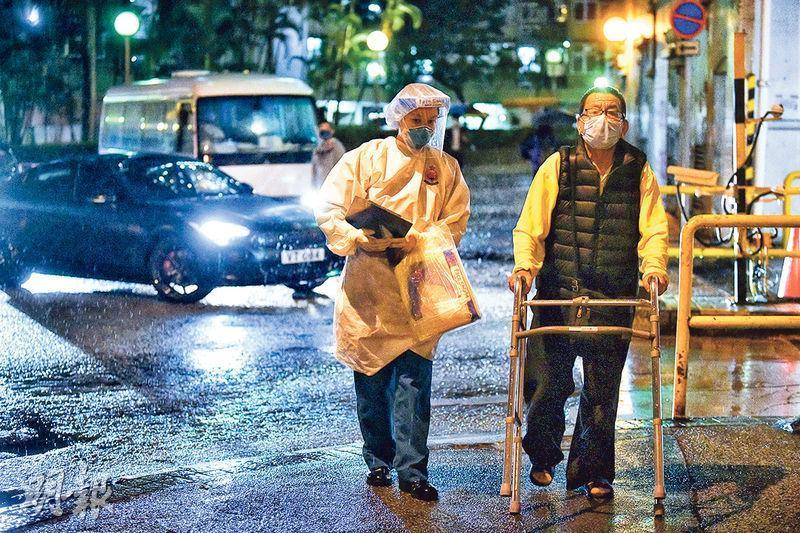 一名不良於行的愛和樓居民在穿保護衣的人員陪同下登上小巴,其間該居民需拄着助行架冒雨步行近百米,之後撤離的長者才有人協助撐傘擋雨。(梁銘康攝)