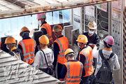 建造業界昨起推出試行措施,要求工人必須持有14天有效檢測陰性證明才能進入地盤。本報記者昨早觀察港鐵沙中線會展站地盤,一名職員(白帽)手持檢測器為入閘工人量體溫,當多名工人一齊入閘,單獨一名職員難以為每個工人量度體溫。(李紹昌攝)