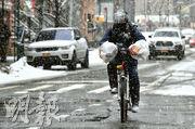 美國東北部近日亦出現暴雪天氣。在紐約布魯克林區,昨有民眾冒着風雪騎單車出行。(法新社)