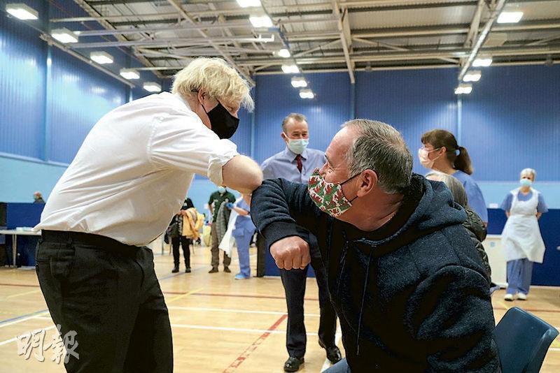 英國首相約翰遜(左)周三到訪南威爾斯一個用作疫苗注射中心的運動場館,與一名等候接種新冠疫苗的男子碰手肘打招呼。(路透社)