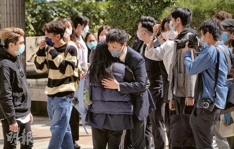 第三被告學生陳子斌(中、黑白格仔口罩者)在庭外與親友相擁,他隨後表示沒想過案件過後有什麼可做,仍擔心律政司會上訴。(楊柏賢攝)