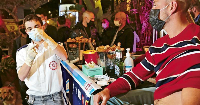 以色列的新冠疫苗接種人員周四去到特拉維夫的酒吧,準備給民眾注射疫苗。以色列是全球接種新冠疫苗人口比例最高的國家。(法新社)