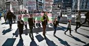 希臘雅典周二(23日)有一批年輕難民跟醫護人員一同上街,要求當局為難民提供社會保障和納入疫苗接種項目,有人舉起寫上「難民的命也是命」的標語。(法新社)