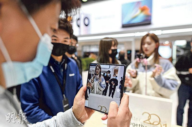 華為最新的折疊屏手機Mate X2昨日在內地開售,不僅立即售罄,更在炒賣風氣下推高二手市場價格。圖為本月23日在上海舉辦的世界移動通信大會中,一名參觀者試用Mate X2。(法新社)
