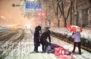 被冷空氣影響,中國中東部地區出現大範圍雨雪降溫。河南鄭州市前晚突降大雪,一名駕駛電單車的市民跌倒,途人上前幫忙。(新華社)