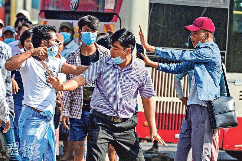 一名緬甸軍方支持者(前左)昨日手持利器,在仰光街頭與支持民主的示威者爭執。(路透社)