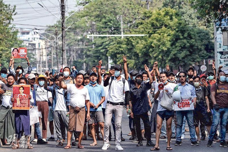 昨天參與示威的部分仰光民眾,繼續做出反專制的三指禮手勢。(法新社)